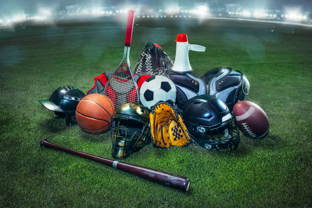Sports balls on the field with yard line. Soccer ball, American football and Baseball in yellow glove on green grass. Outdoors stock photo