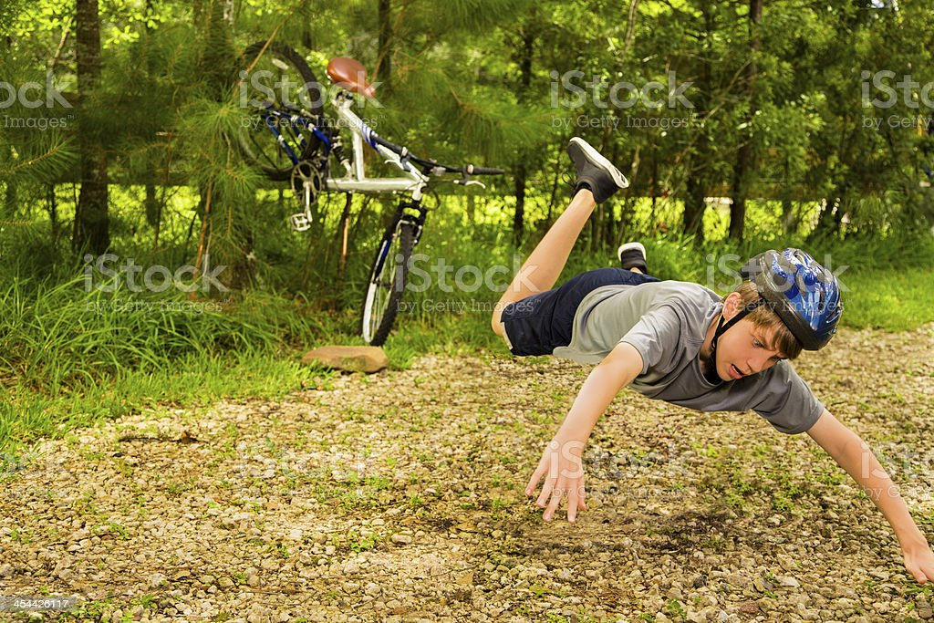 Sports:  Boy having bicycle accident on gravel road. stock photo