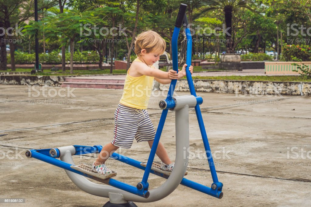 sports boy trains on elliptical cross trainer stock photo