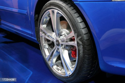 Blue sports car´s alloy wheel with red brake.