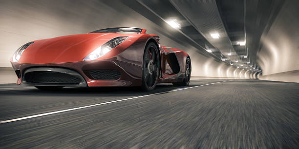 Sports Car in a Tunnel A red sports car speeding through a tunnel. This car is designed and modelled by myself. Very high resolution 3D render. All markings are ficticious. concept car stock pictures, royalty-free photos & images