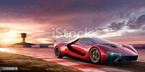 A close up image of a generic red sports car moving at high speed on a racetrack at beautiful dramatic and colourful sky at sunset. The location is fictional, and observation tower is visible in the background. Selective focus, with car in focus and motion blur on foreground.