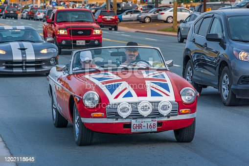 Moncton, New Brunswick, Canada - July 11, 2015 : Male driver and female passenger cruise in a 1976 MGB sports car Saturday evening on Mountain Road during 2015 Atlantic Nationals Automotive Extravaganza.