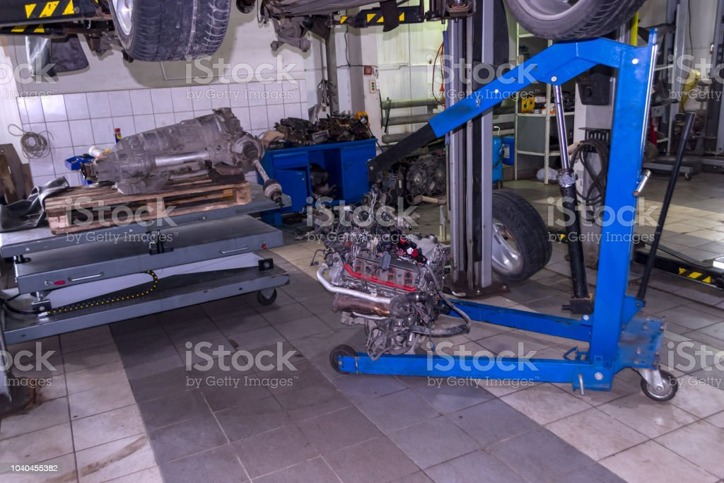 A sports car raised on a lift for repair and under it a detached engine suspended on a blue crane and a gear box on a lifting table in a vehicle repair shop stock photo