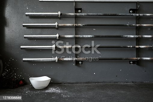 Exercise equipment at an empty gym, barbells on a rack and a chalk, talcum powder bowl.