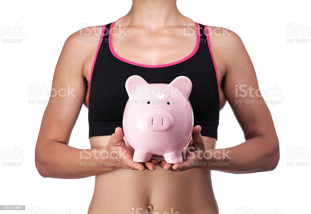 sports coach holding a piggy bank stock photo
