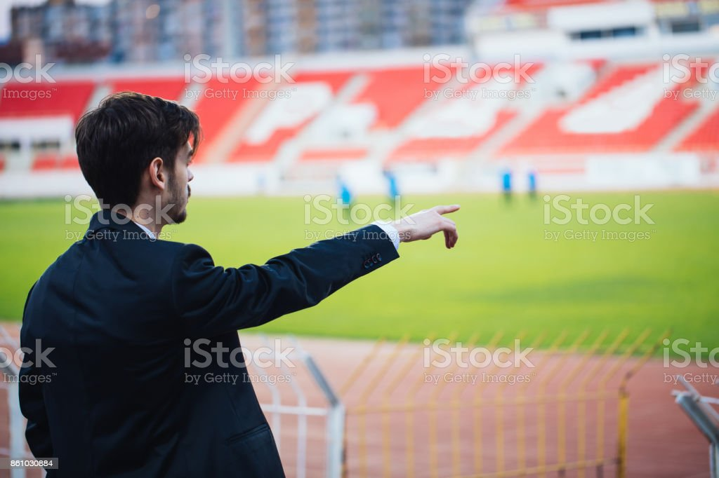 One man, young and handsome, soccer manager on the bleacher.
