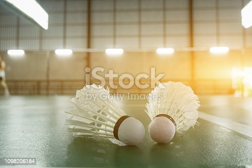 sports concept.Badminton ball (shuttlecock) and racket ,badminton courts with players competing modern gym in background,selective focus,vintage color