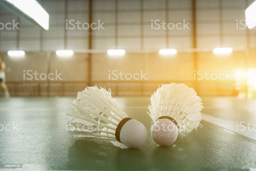 Cтоковое фото sports concept.Badminton ball (shuttlecock) and racket ,badminton courts with players competing modern gym in background,selective focus,vintage color