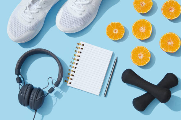 Sports equipment and accessories, shoes, dumbbells, notebook and oranges on blue background stock photo