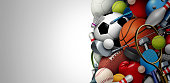 Sports equipment background with a football basketball baseball soccer tennis and golf ball including ping pong tennis hockey puck as healthy recreation including copy space with 3D illustration elements.