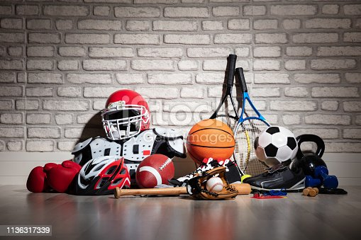 Various Sport Equipment On Floor In Front Of Brick Wall