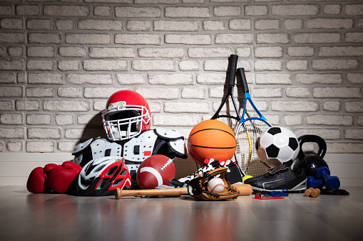 Various Sport Equipment On Floor In Front Of Brick Wall