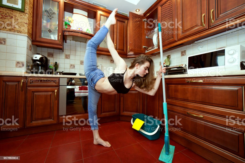 Sports exercises during house cleaning. stock photo