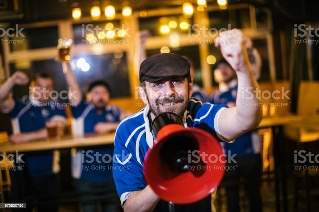 Man yelling through the red megaphone while watching the game