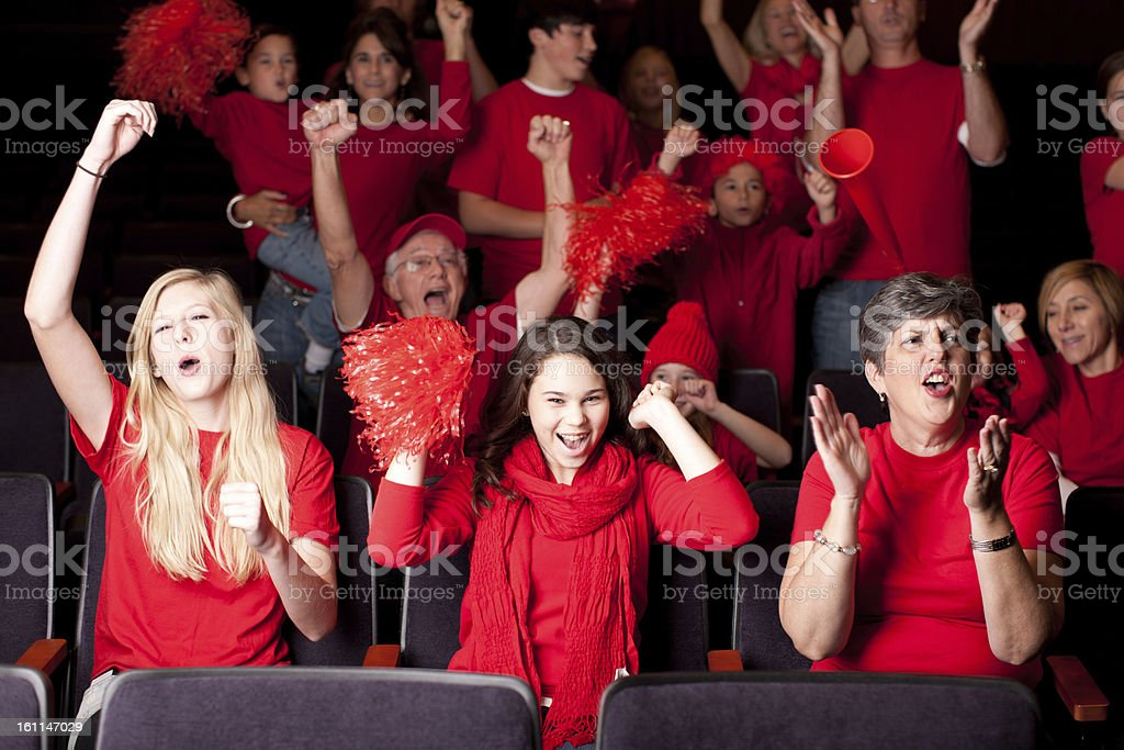 A group of real adult and children sports fans are excited spectators...
