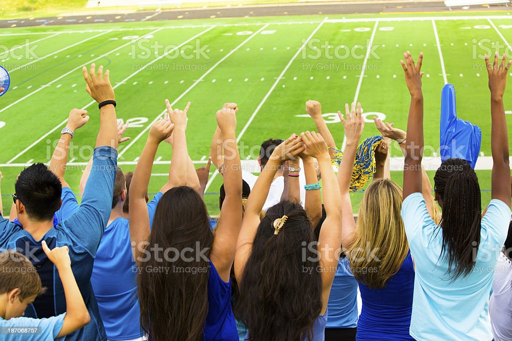 Sports: Fans cheer for their team during football game. royalty-free stock photo