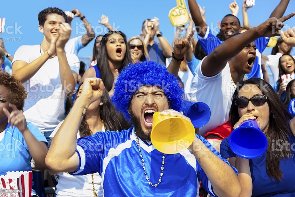 Multi-ethnic group of fans scream and yell for their team to win...
