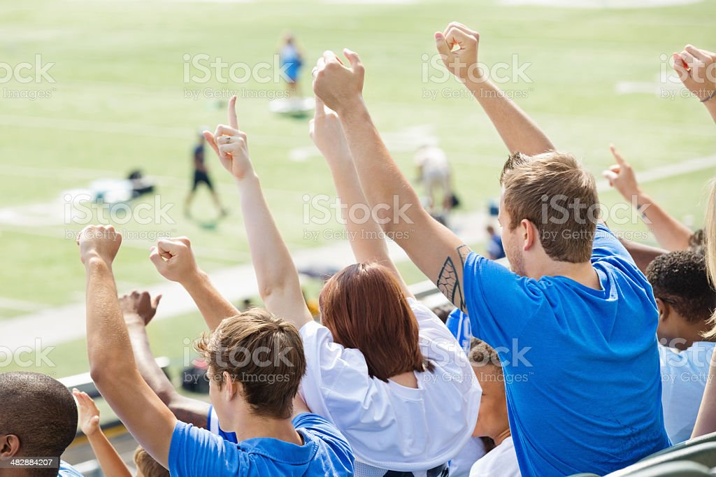 Sports fans cheering for players during game on field stock photo