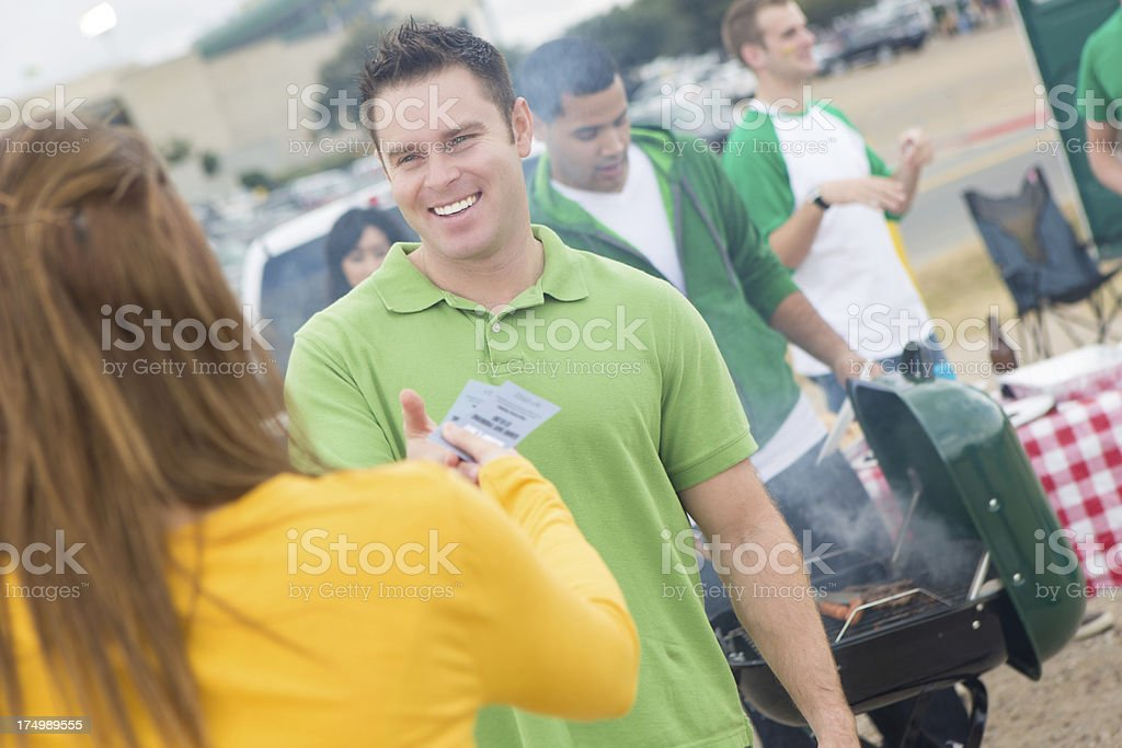 Sports fans exchanging tickets at tailgate party cookout stock photo