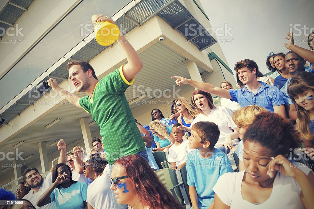 Sports fans heckling fan from opposing team in bleachers