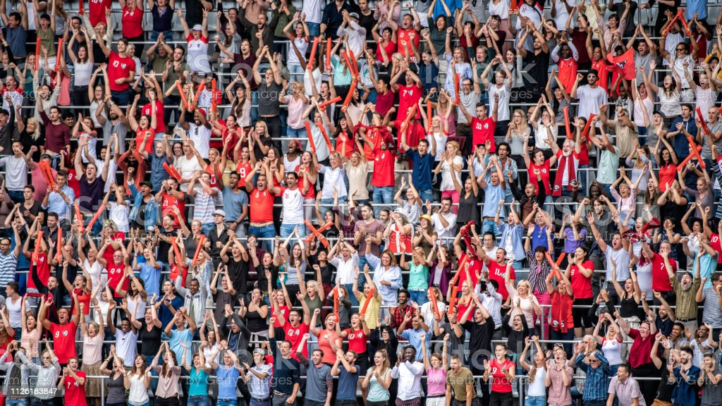 Sports Fans In Red Jerseys Cheering On Stadium Bleachers Stock Photo - Download Image Now
