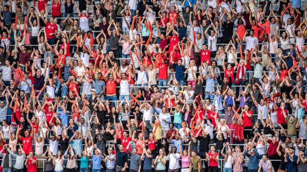 Sports fans in red jerseys cheering on stadium bleachers Large crowd of people, some wearing red sports jerseys, cheering and clapping on stadium bleachers. spectator stock pictures, royalty-free photos & images