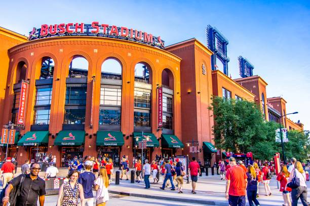 Sports fans outside of Busch Stadium in the evening St. Louis, MO—June 6, 2018 crowds walk outside of baseball stadium prior to game.  Busch Stadium is home to Major League Baseball's Saint Louis Cardinals team. major league baseball stock pictures, royalty-free photos & images