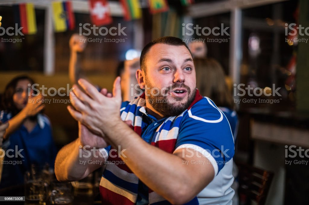 Group of people watching sport game being excited and emotional
