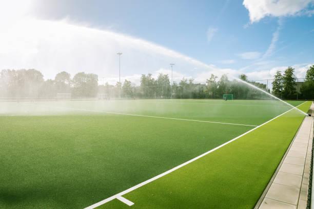 sportveld wordt besproeid door een sprinklerinstallatie - dutch hockey stockfoto's en -beelden