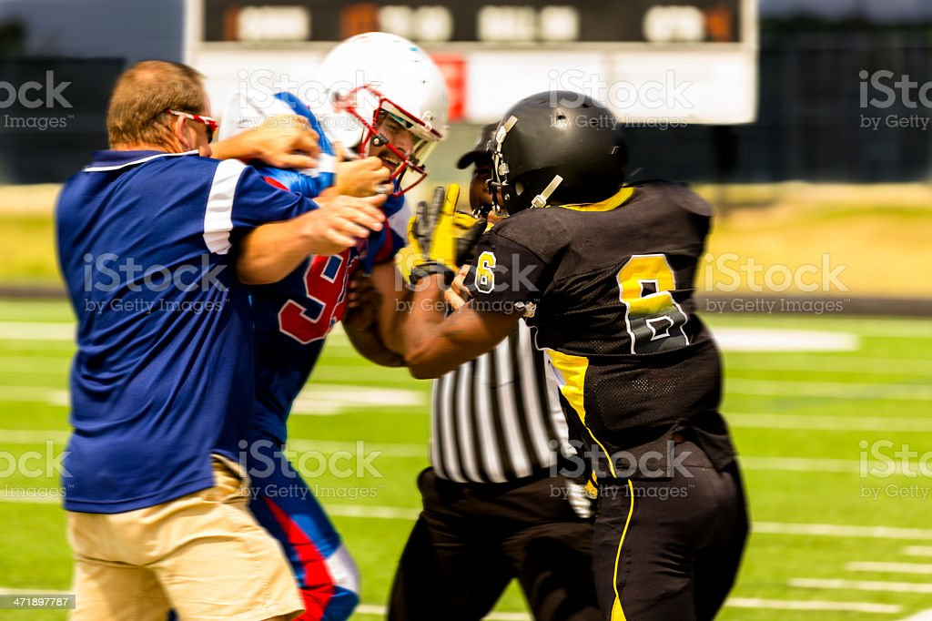 Sports:  Football players separated by coach, referee during game. stock photo
