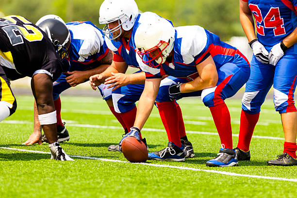 Sports: Football team prepares for play.  Line of scrimmage. Center prepares to hike the football to the quarterback. Line of scrimmage.   line of scrimmage stock pictures, royalty-free photos & images