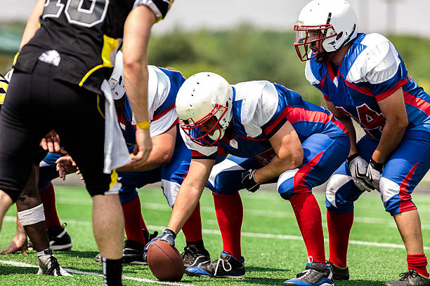 Sports: Football teams prepare for a play.  Line of scrimmage. Center prepares to hike the football to the quarterback. Line of scrimmage.  line of scrimmage stock pictures, royalty-free photos & images