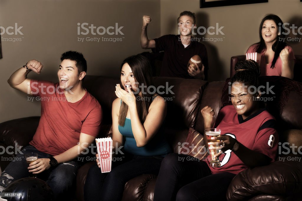 Sports: Friends cheer after their team scores. Media room. stock photo