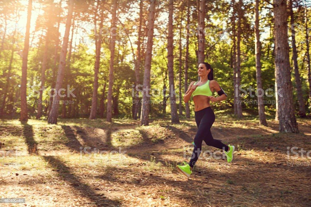 Sports girl brunette runs through the forest. stock photo