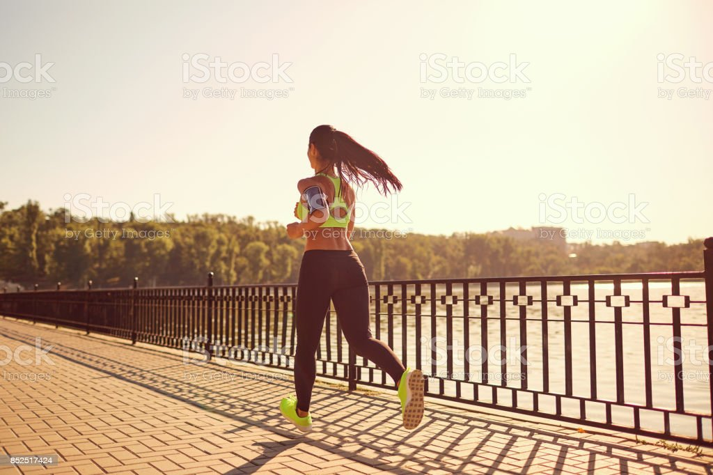 A sports girl runs through the park by the lake. stock photo