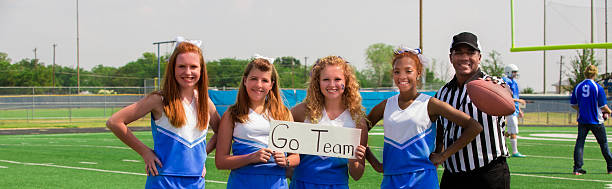 Sports: Group of cheerleaders and referee. Football players background. stock photo