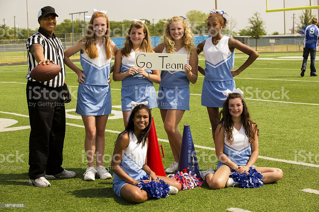 Sports:  Group of cheerleaders and referee with 'go team' sign. stock photo