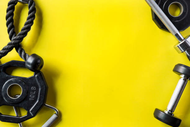 sports gym equipment on yellow background - health club stock photos and pictures