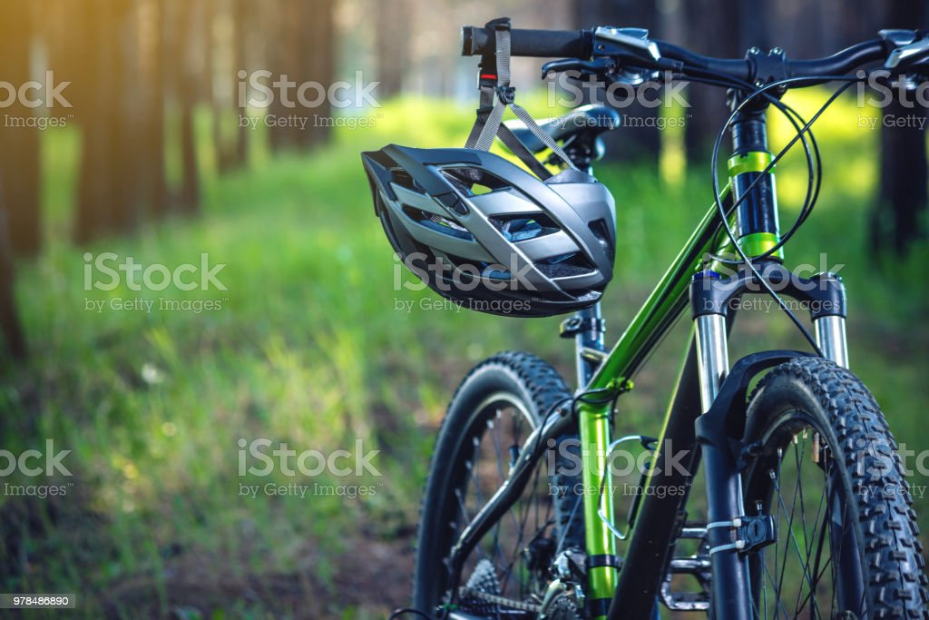 Sports helmet on a green mountain bike in the Park. Concept protection during active and healthy lifestyle stock photo