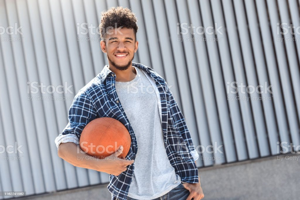 Young mulatto man standing isolated on city street holding basketball...
