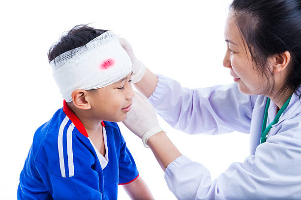 Sports injury. Doctor makes bandage on head patient, on white. stock photo