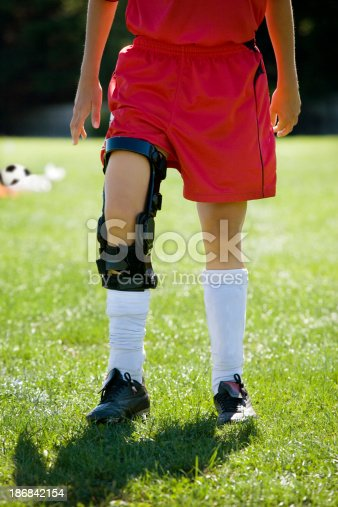 Female soccer player wearing lightweight knee ligament brace. ACL support.