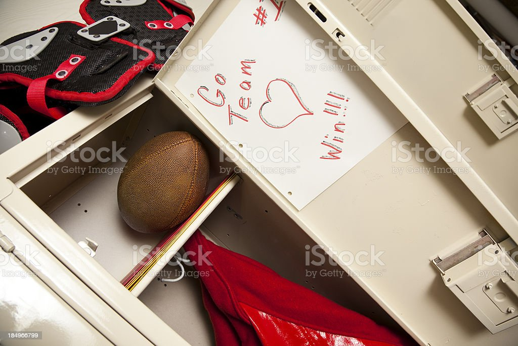 Sports locker with jacket, football and shoulder pads stock photo