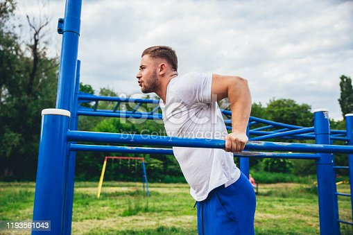 Young sports man doing exercise on parallel bar outdoor