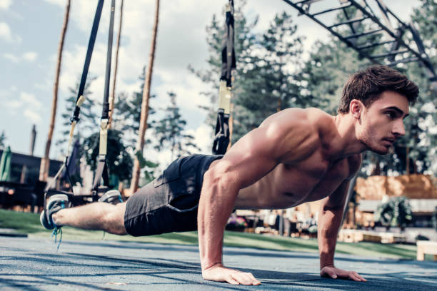 sports man doing suspension training - push up stock photos and pictures