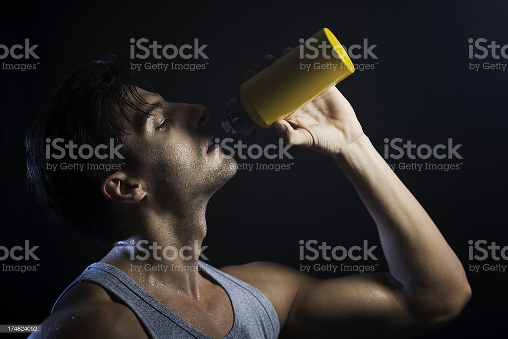 Sports man drinking on black background, horizontal. royalty-free stock photo