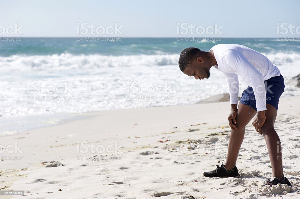 Sports man exhausted after work out with hands on knees stock photo