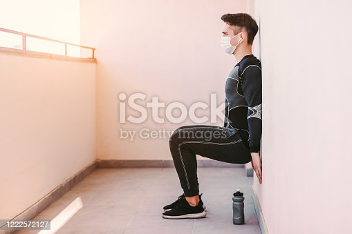 Young sporty man fitness coach in medical face mask squatting against wall on balcony. Confident sports man in protective mask doing wall leg sit exercise at home gym. COVID-19 quarantine, workout