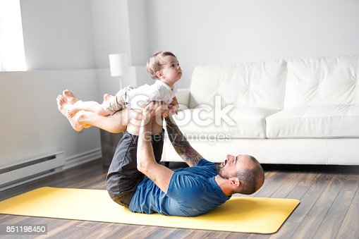 istock sports man is engaged in fitness and yoga with a baby at home 851198450